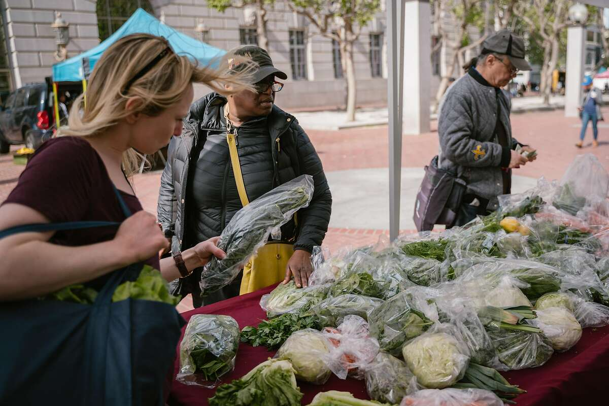 Julia Winfield (left) chooses produce to purchase at the Heart of the City Farmers Market in San Francisco, Calif., on Sunday, April 28, 2019. CalFresh will expand to people on Social Security Income (SSI) and allow up to $200 a month for healthy foods.