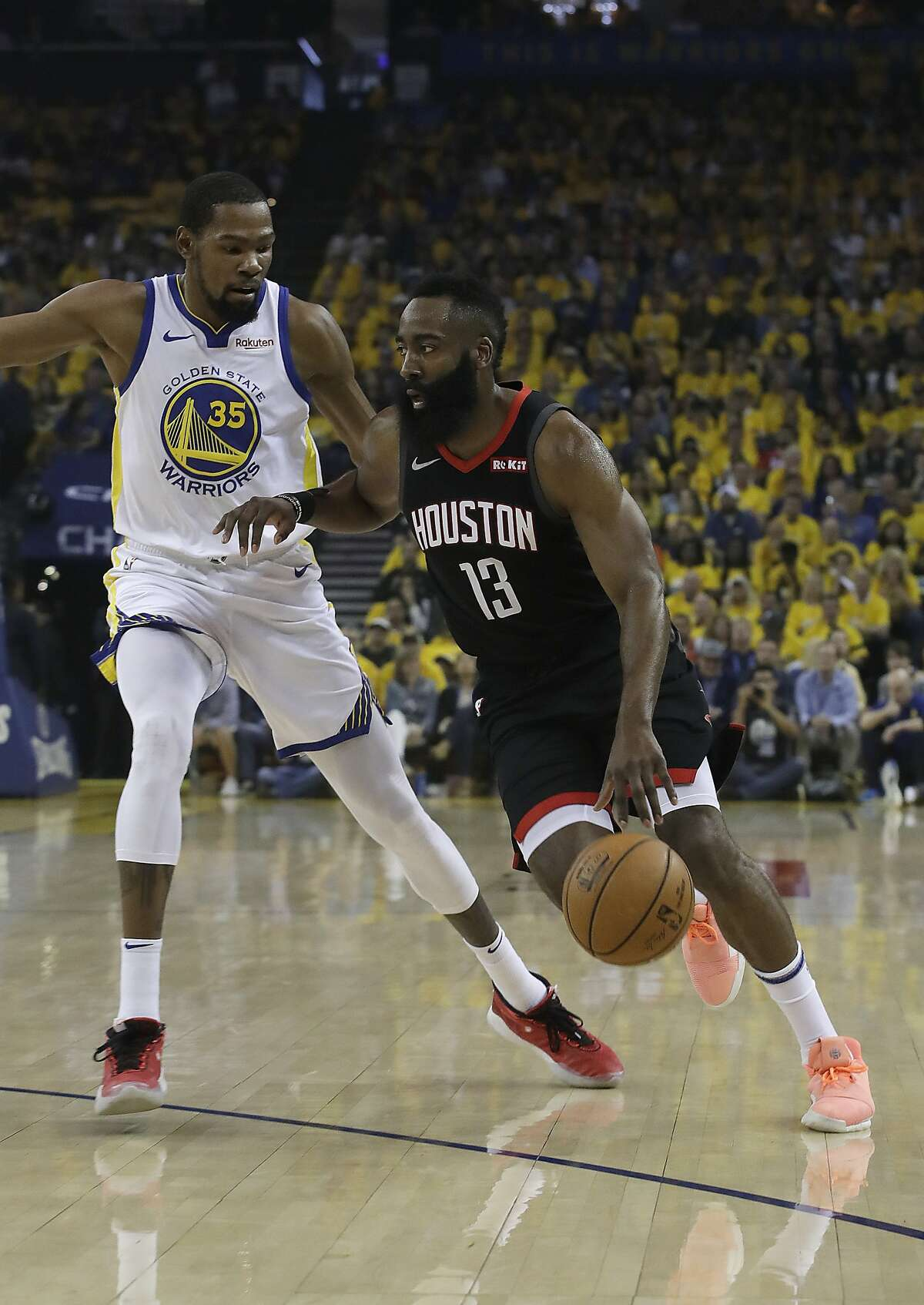 Houston Rockets guard James Harden (13) drives against Golden State Warriors forward Kevin Durant (35) during the first half of Game 1 of a second-round NBA basketball playoff series in Oakland, Calif., Sunday, April 28, 2019. (AP Photo/Jeff Chiu)