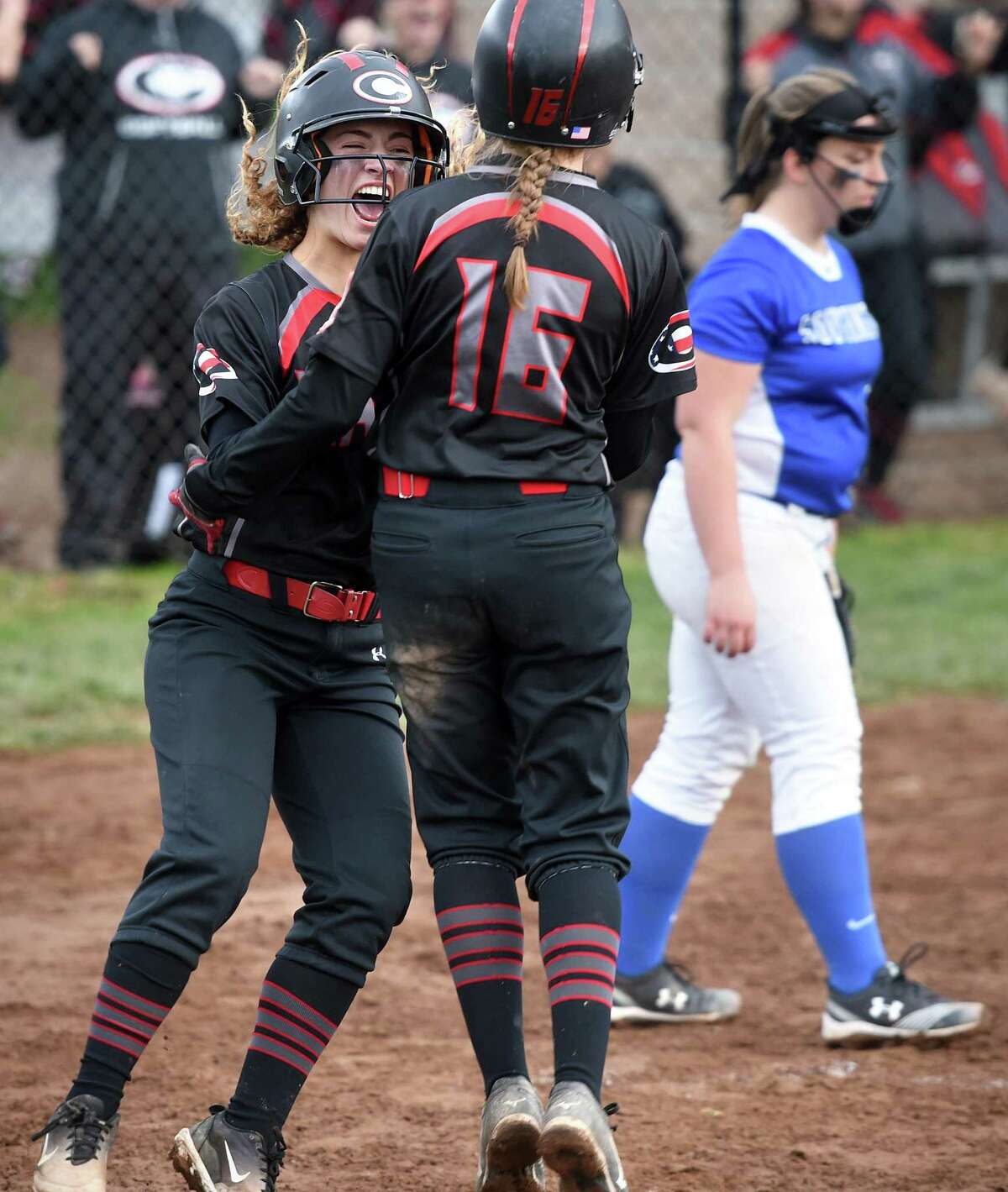 Cheshire's Sophia Vagts, left, and Sarah Capute celebrate after scoring in the seventh inning against Southington to tie the game at 3 on Tuesday.