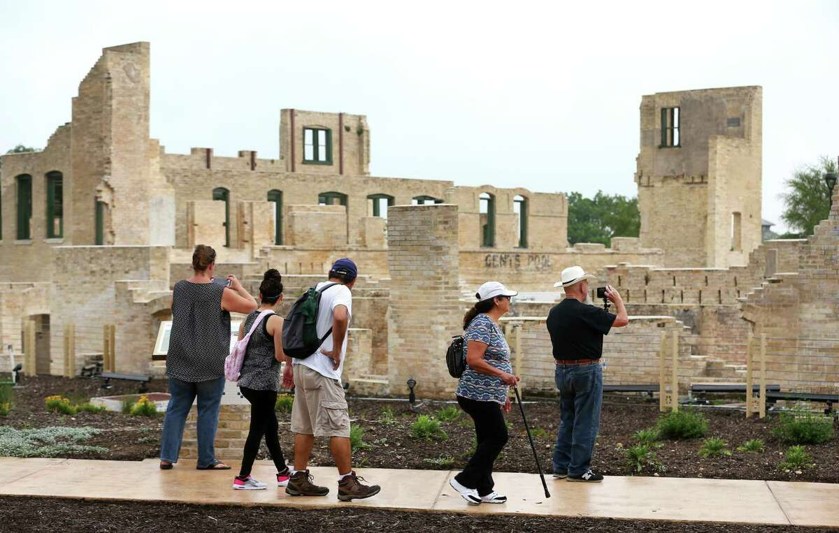 People walk past the former Hot Wells Hotel during the grand opening of the Hot Wells of Bexar County Park last year. The county stabilized the once-crumbling building while turning the 4-acre site into a park connected to the Mission Reach section of the San Antonio Riverwalk.