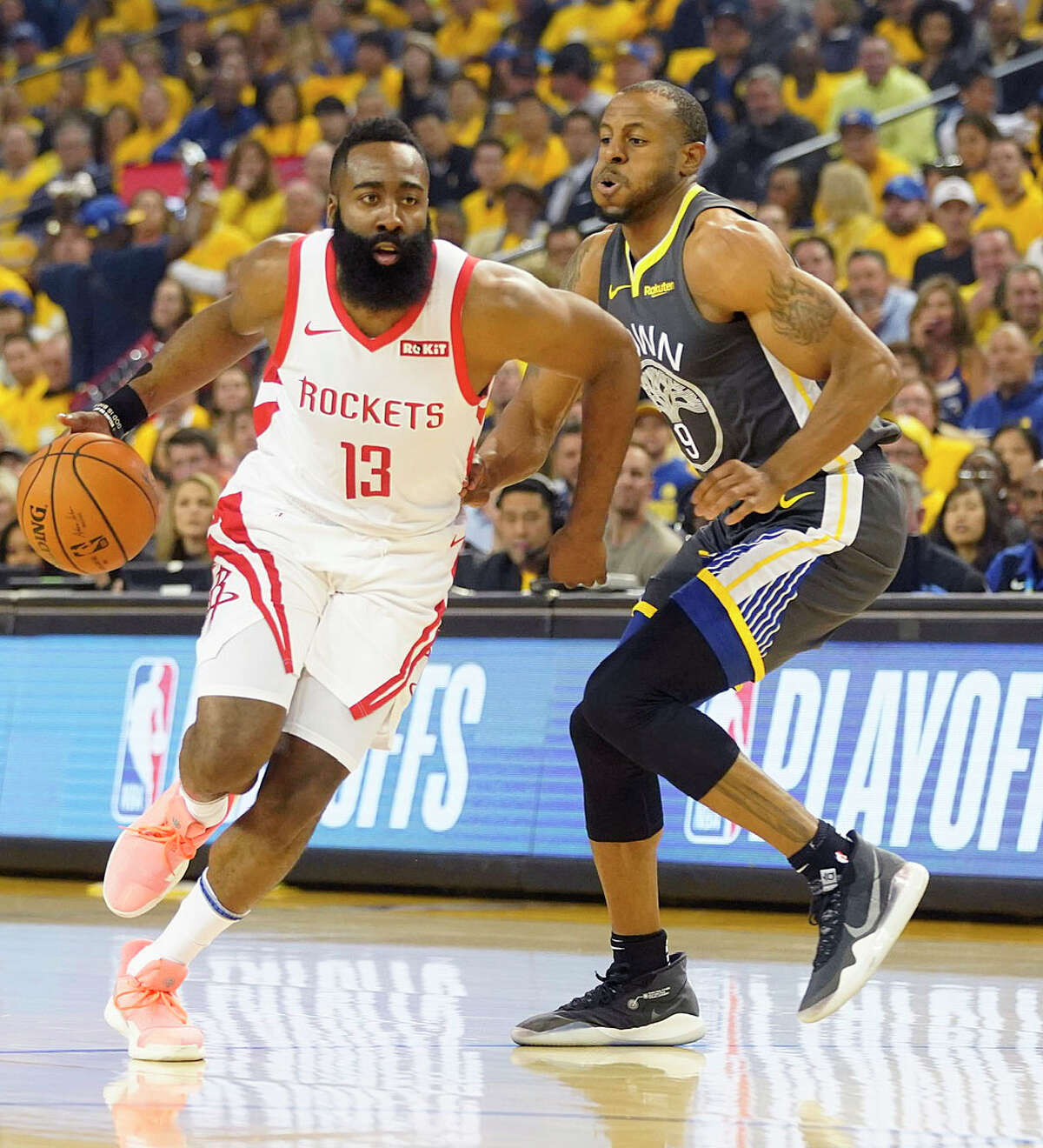Houston Rockets guard James Harden (13) drives past Golden State Warriors guard Andre Iguodala (9) during the first half of an NBA playoff game at Oracle Center, Tuesday, April 30, 2019, in Oakland .