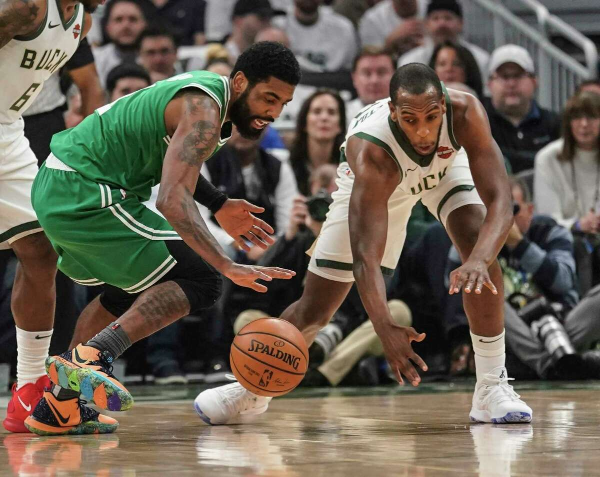Milwaukee Bucks' Khris Middleton and Boston Celtics' Kyrie Irving go after a loose ball during the first half of Game 2 of a second round NBA basketball playoff series Tuesday, April 30, 2019, in Milwaukee. (AP Photo/Morry Gash)