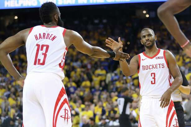 Houston Rockets guards Chris Paul (3) and James Harden (13) celebrate as they closed the gap during the second half of Game 2 of an NBA playoff game at Oracle Arena, Tuesday, April 30, 2019, in Oakland .