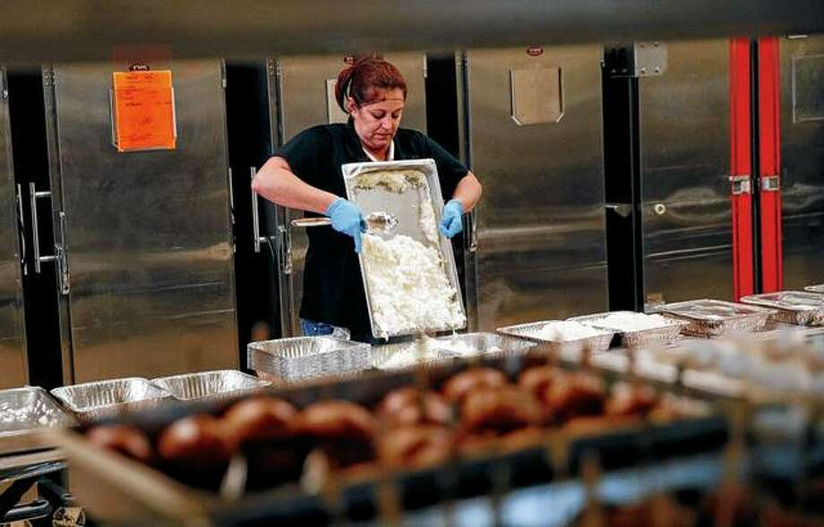 Lisa Garcia packs up uneaten food from the convention area at the Aria resort-casino in Las Vegas. The food will be redistributed by Three Square, southern Nevada's only food bank. Photo: John Locher | Associated Press