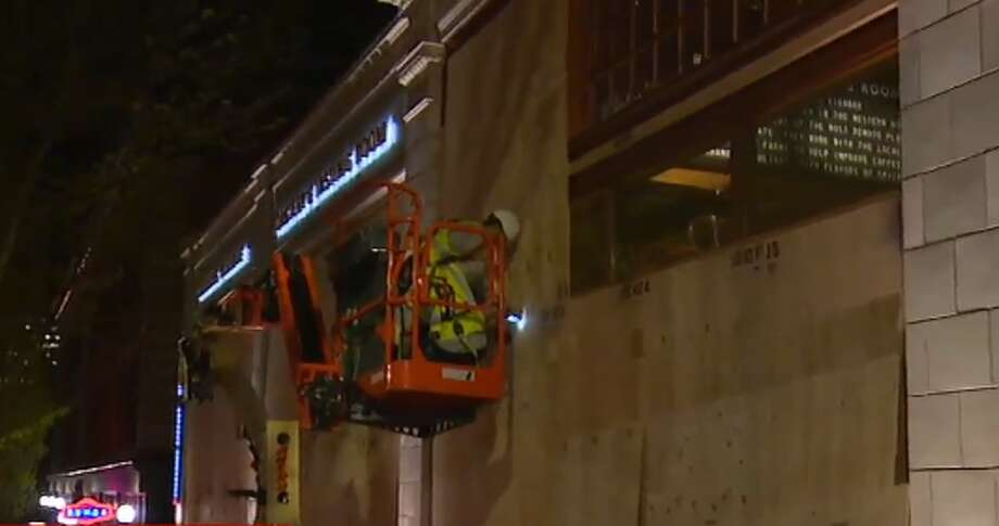 Crews board up windows outside the Starbucks Reserve Roastery on Seattle's Capitol Hill on the night of April 30, 2019 in preparation for May Day. Photo: Courtesy KOMO