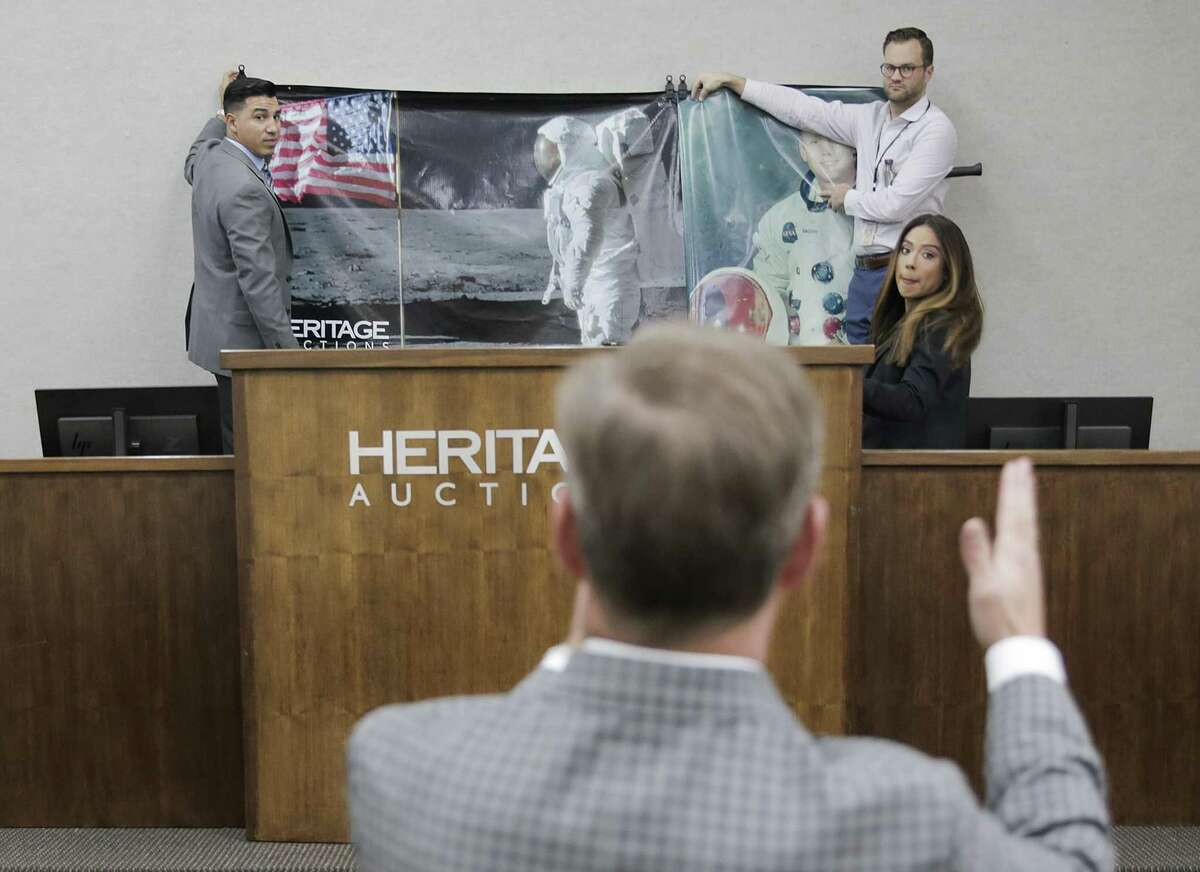 Auctioneer Mike Sadler gives direction for a banner behind the stage for the auction of Neil Armstrong's memorabilia at Heritage Auctions Dallas on Thursday, Nov. 1, 2018.