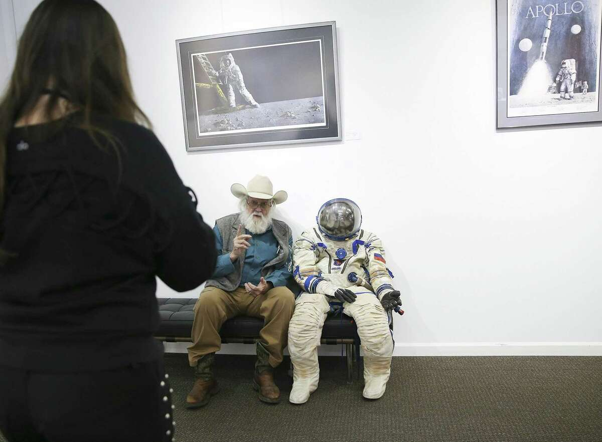 Lionel Bevan III poses for a photo with a cosmonaut outfit during the auction of Neil Armstrong's memorabilia at Heritage Auctions Dallas on Thursday, Nov. 1, 2018.