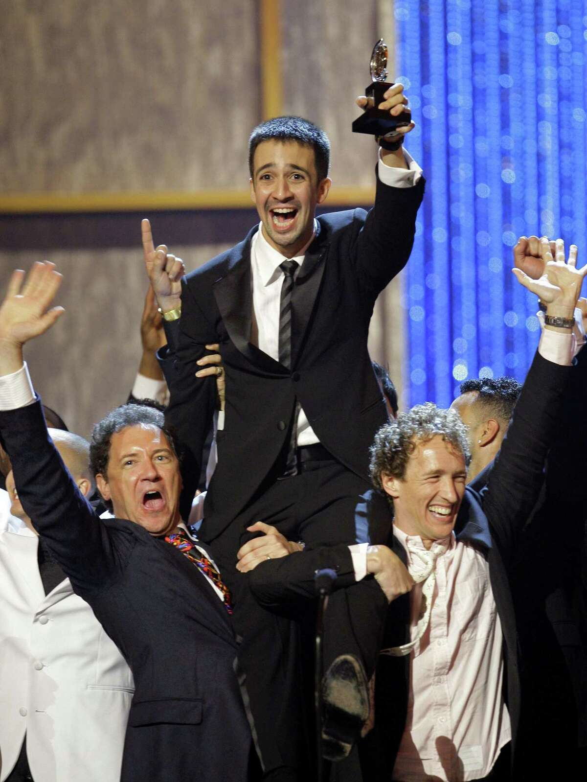 Lin-Manuel Miranda, center, is hoisted up on stage after