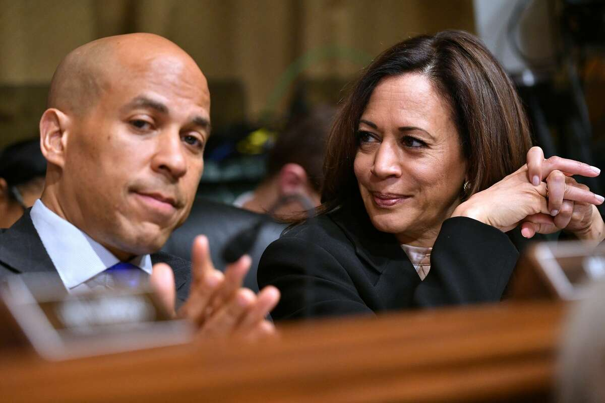 US Senators Cory Booker (L) and Kamala Harris listen as US Attorney General William Barr prepares to testify before the Senate Judiciary Committee on