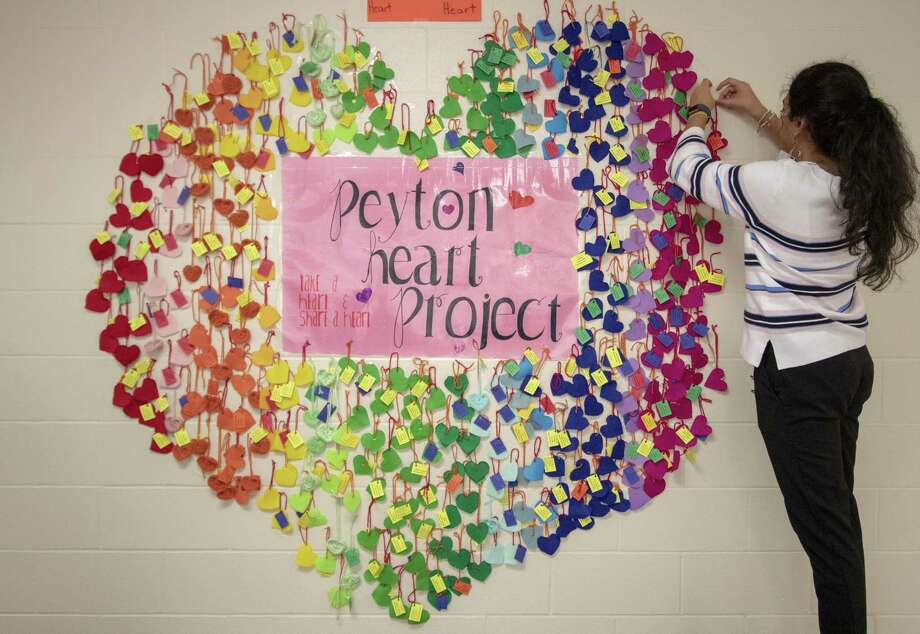 College Park senior Hamsini Ajjan hangs hearts as part of the Peyton Heart Project on Tuesday, April 30, 2019 at The Woodlands College Park High School in The Woodlands. The Woodlands College Park High School students create a project every year to help those struggling with suicide by taping hearts with positive messages to one of the walls at the school. Photo: Cody Bahn, Houston Chronicle / Staff Photographer / © 2018 Houston Chronicle