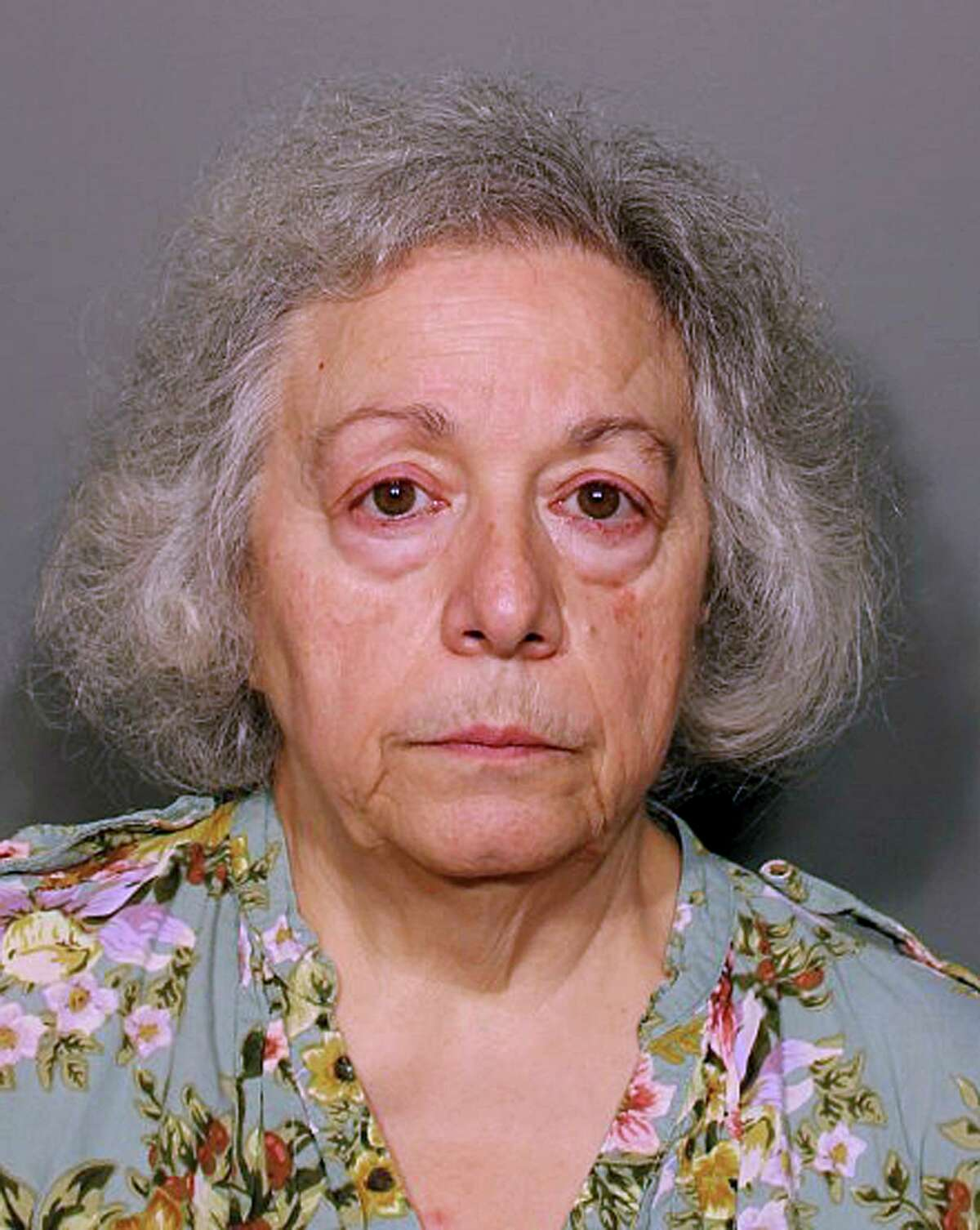 This booking photo released Monday, Aug. 13, 2018, by the New Canaan Police Department shows Marie Wilson, of Wilton, Conn., a former cafeteria worker who along with her sister Joanne Pascarelli was charged with stealing nearly a half-million dollars from New Canaan, Conn., schools over the last five years. (New Canaan Police Department via AP)