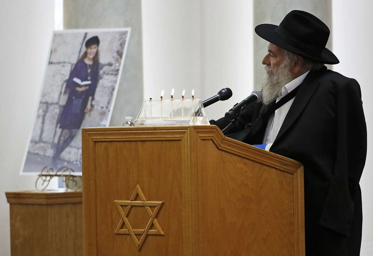 CORRECTS SPELLING OF RABBI'S FIRST NAME TO YISROEL INSTEAD OF YISHOEL - Yisroel Goldstein, Rabbi of Chabad of Poway, speaks Monday, April 29, 2019, at the funeral for Lori Kaye, who is pictured at left, in Poway, Calif. Kaye was was killed Saturday when a gunman opened fire inside the Chabad of Poway synagogue. Goldstein was injured in the shooting. (AP Photo/Gregory Bull)