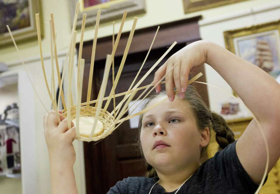 Charley Landers works on weaving a basket during the annual Pioneer Camp at the Heritage Museum of Montgomery County, Wednesday, July 19, 2017, in Conroe. Area children ages 8 to 11 learn from volunteers about early life in America and the history of the county during the two-week camp. Registration opens on Thursday, May 9, for this year's camp. Photo: Jason Fochtman, Staff Photographer / Houston Chronicle / © 2017 Houston Chronicle