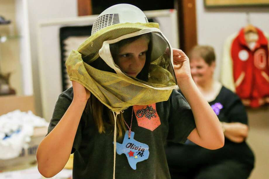 Pioneer Camp attendee Olivia McGuire tries on a beekeeping suit on Monday, July 9, 2018, at the Heritage Museum in Conroe. Registration continues at the Heritage Museum of Montgomery County for this year's camp July 8-12 and July 15-19. Photo: Michael Minasi, Staff Photographer / Houston Chronicle / © 2018 Houston Chronicle