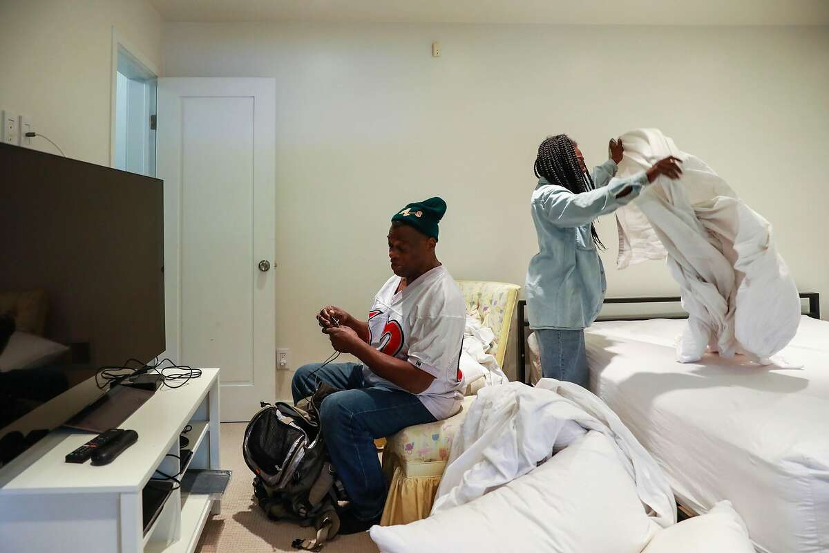 Greg Dunston, Sr., 61, converses with partner, Marie Mckinzie, 54, as she makes up their bed in Piedmont, Calif., on Thursday, April 18, 2019. Greg and Marie moved into a basement apartment in Piedmont after living on the streets of Oakland on and off for ten years.