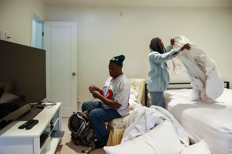 Dunston converses with Mckinzie as she makes their bed. The residence where they're living is worth millions. Photo: Yalonda M. James / The Chronicle