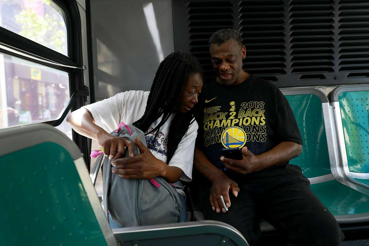 Marie Mckinzie, 54, and her partner Greg Dunston, Sr., 61, ride on a bus through downtown Oakland following a visit to the HOPE-HOME Study (Health Outcomes of People Experiencing Homelessness on Older Middle Age) office in Oakland, Calif., on Wednesday, April 24, 2019.