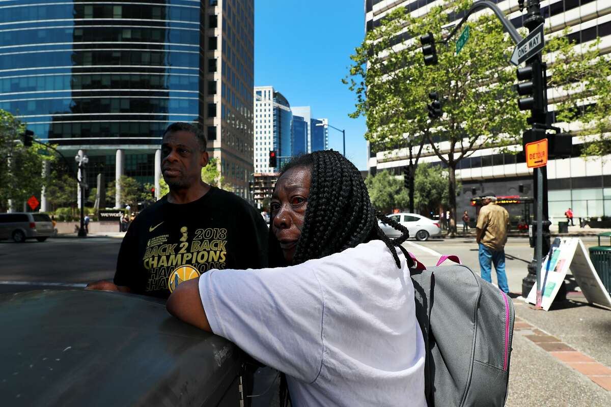 Greg Dunston, Sr., 61, and his partner Marie Mckinzie, 54, wait to catch a bus at 12th and Broadway following a visit to the HOPE-HOME Study (Health Outcomes of People Experiencing Homelessness on Older Middle Age) office in Oakland, Calif., on Wednesday, April 24, 2019.