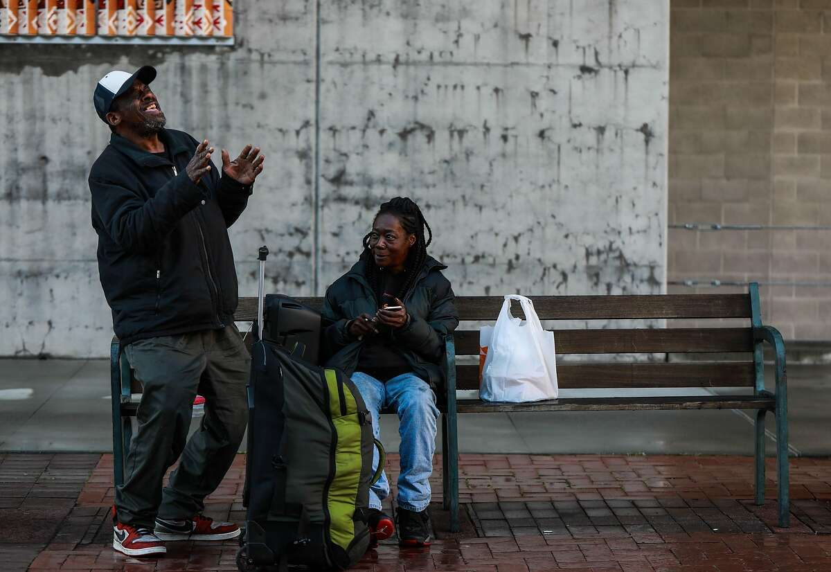 Greg Dunston, Sr., 60, sings a song to his partner Marie Mckinzie, 54, as they relax near the Amtrak Station at Jack London Square in Oakland, Calif., on Saturday, March 2, 2019. The couple moved into a basement apartment in Piedmont in February after living on the streets.