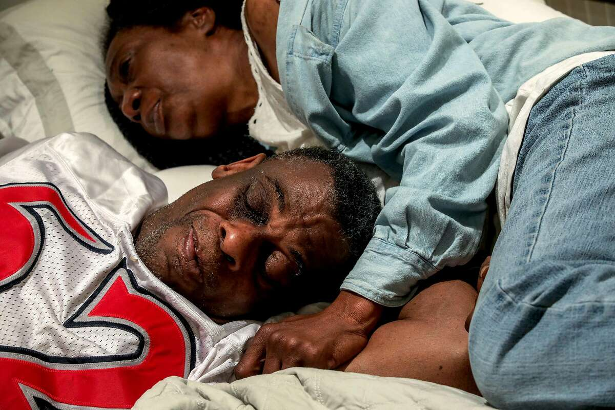 Marie Mckinzie, 54, and her partner, Greg Dunston, Sr., rest in bed inside their basement apartment where they've been living since February, in Piedmont, Calif., on Thursday, April 18, 2019. Greg and Marie had been watching Game 3 of the NBA playoffs between the Golden State Warriors and the LA Clippers. Previously, the couple lived on the streets of Oakland.