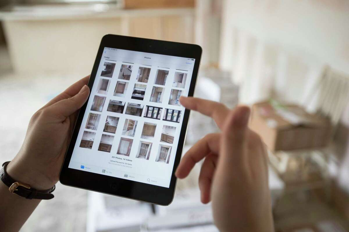 Bailee Wright, transaction coordinator for Entera, scrolls through photos she took of progress on a home remodel for an institutional investor on Friday, March 8, 2019, in Houston.