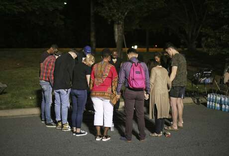 People gathered for a prayer at a staging area near the University of North Carolina Charlotte after a shooting on campus left two students dead and four other people injured on Tuesday, April 30, 2019.