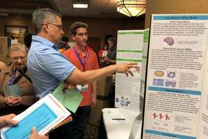 A judge talks to senior Collin Marino about his poster, which earned honorable mention at the Junior National Science and Humanities Symposium. Four GHS students presented original scientific research papers and posters in Albuquerque, N.M., alongside 226 other qualifying high schoolers.