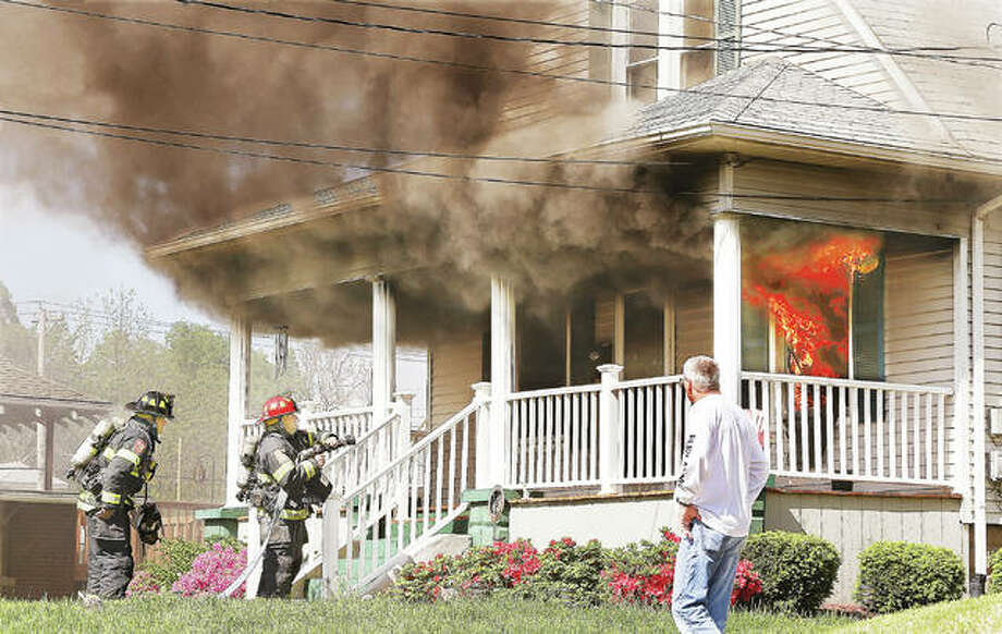 Alton firefighters wait for their hose line to be charged for the initial attack on a fire in a house Wednesday afternoon in the 2500 block of Davis Street in Alton. A neighbor, foreground, who helped pull a supply line into place, walks up for a closer look at the flames coming out a front window. The front of the house sustained extensive fire damage and heavy smoke damage throughout. A mutual aid box alarm brought a second fire department to the scene to assist. A dog was trapped inside the house was killed. A resident managed to escape unharmed. The cause of the fire was under investigation Wednesday afternoon. UPDATE: A man identifying himself as the resident e-mailed The Telegraph Thursday, saying neither he or his wife were home when the fire started and he made every attempt to save his dog.