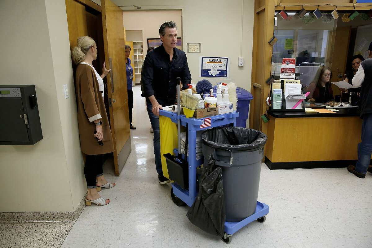 Gov. Gavin Newsom pushes a utility cart while helping the maintenance staff at American River College Wednesday, May 1, 2019, in Sacramento, Calif. Newsom was helping perform work on the campus in honor of May Day, an international holiday honoring laborers and the working class.(AP Photo/Rich Pedroncelli)