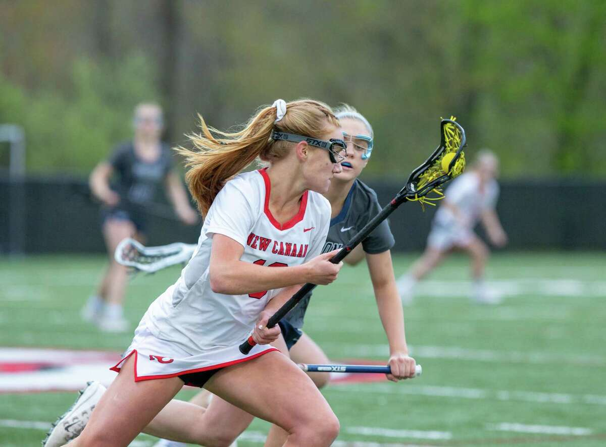 New Canaan's Jane Charlton looks to get past a Wilton defender during a girls lacrosse game Tuesday.