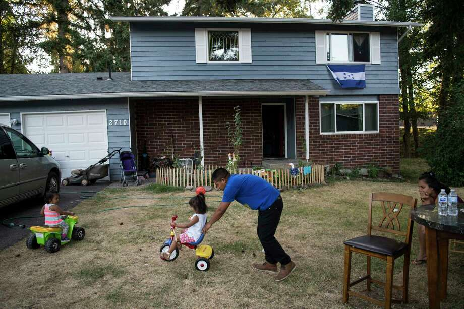Carlos Aldana plays with his daughters Fernanda and Alejandra Aldana-Ramos as his partner Elvia Ramos watches at his sister's house in Seattle, where the family, from Honduras, is staying awaiting a court decision on their asylum cases. President Donald Trump has moved to tighten asylum rules while a massive backlog of immigration cases continue to clog the system. Photo: Washington Post Photo By Carolyn Van Houten. / The Washington Post