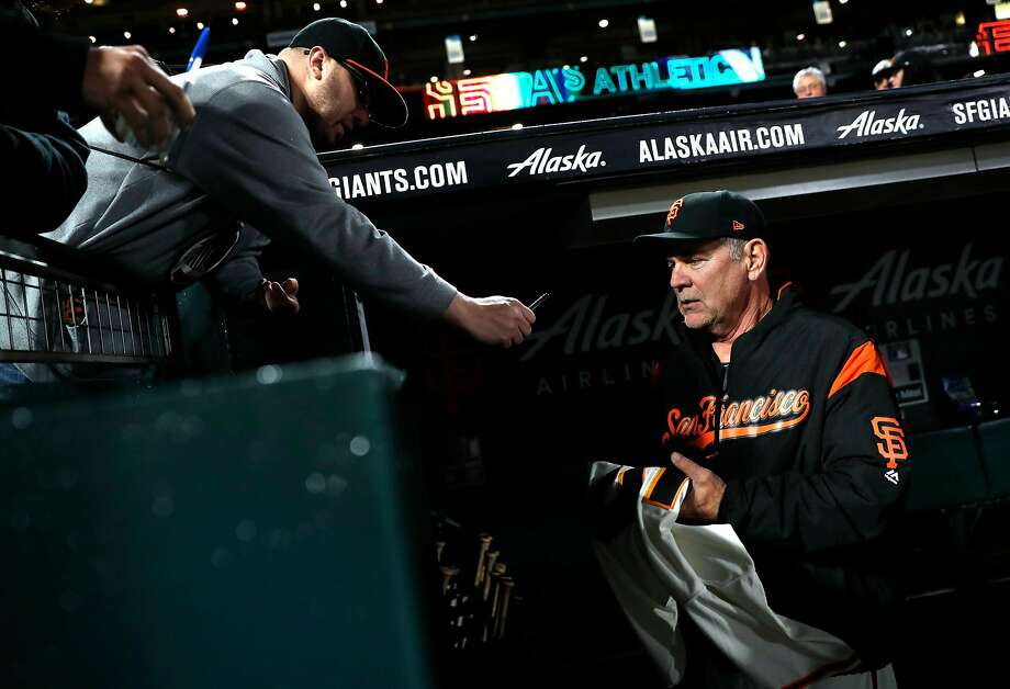 Bochy signs an autograph before the Giants play the Oakland Athletics at Oracle Park. Photo: Scott Strazzante / The Chronicle