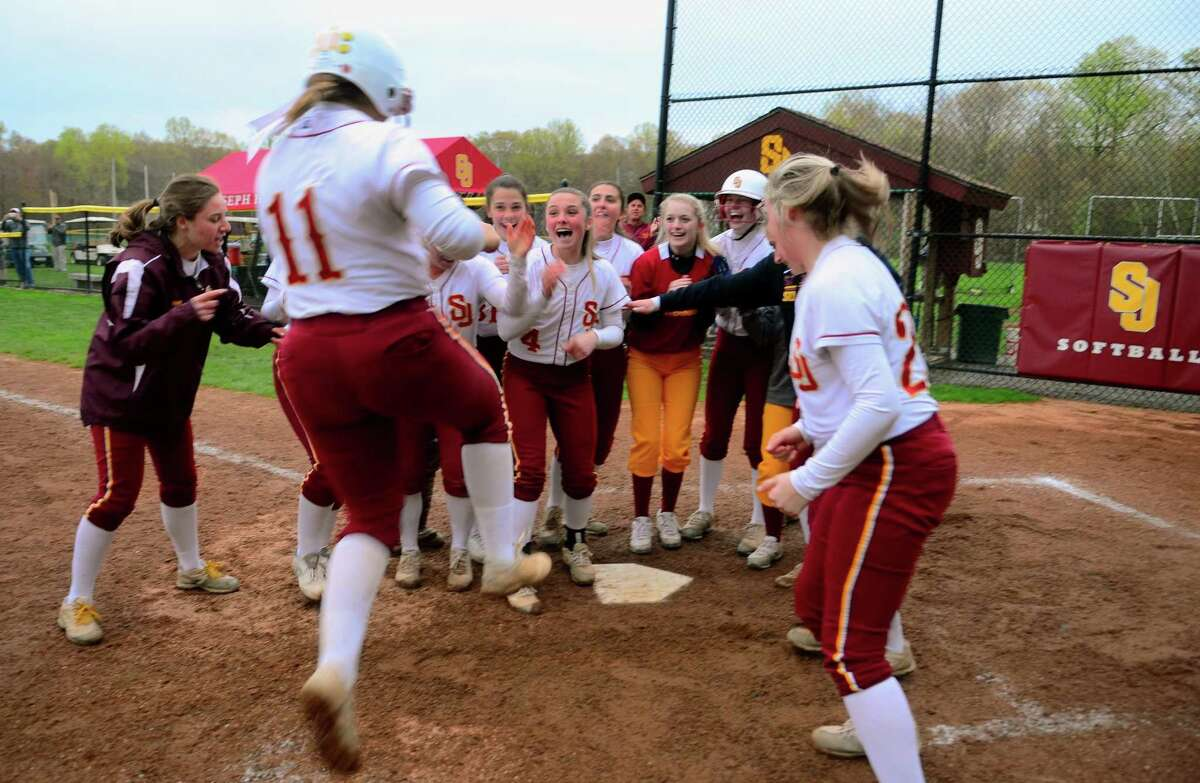 St. Joseph's Charlee Horton (11) lands at home plate after hitting a home run to beat Trumbull 2-1 in the eigth inning of softball action in Trumbull, Conn., on Wednesday May 1, 2019.