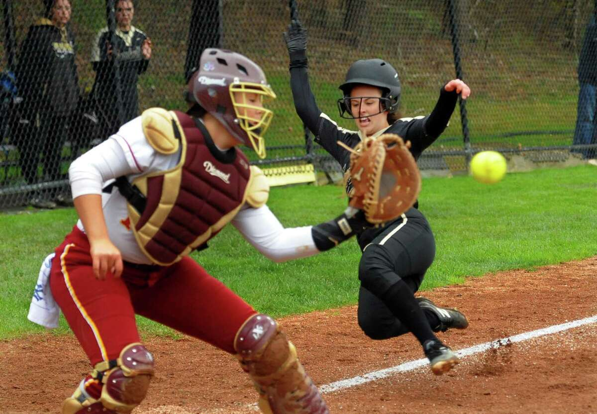 Trumbull's Charlotte Erenberg (4) slides into home plate as St. Joseph catcher Charlee Horton (11) receives the ball for the out during softball action in Trumbull, Conn., on Wednesday May 1, 2019.