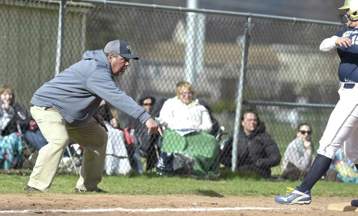 Notre Dame head coach Jeff Bevino tries to get the runner to slide into third during the girls softball game between Notre Dame - Fairfield and New Milford high schools, Wednesday afternoon, April 18, 2018, at New Milford High School, New Milford, Conn.