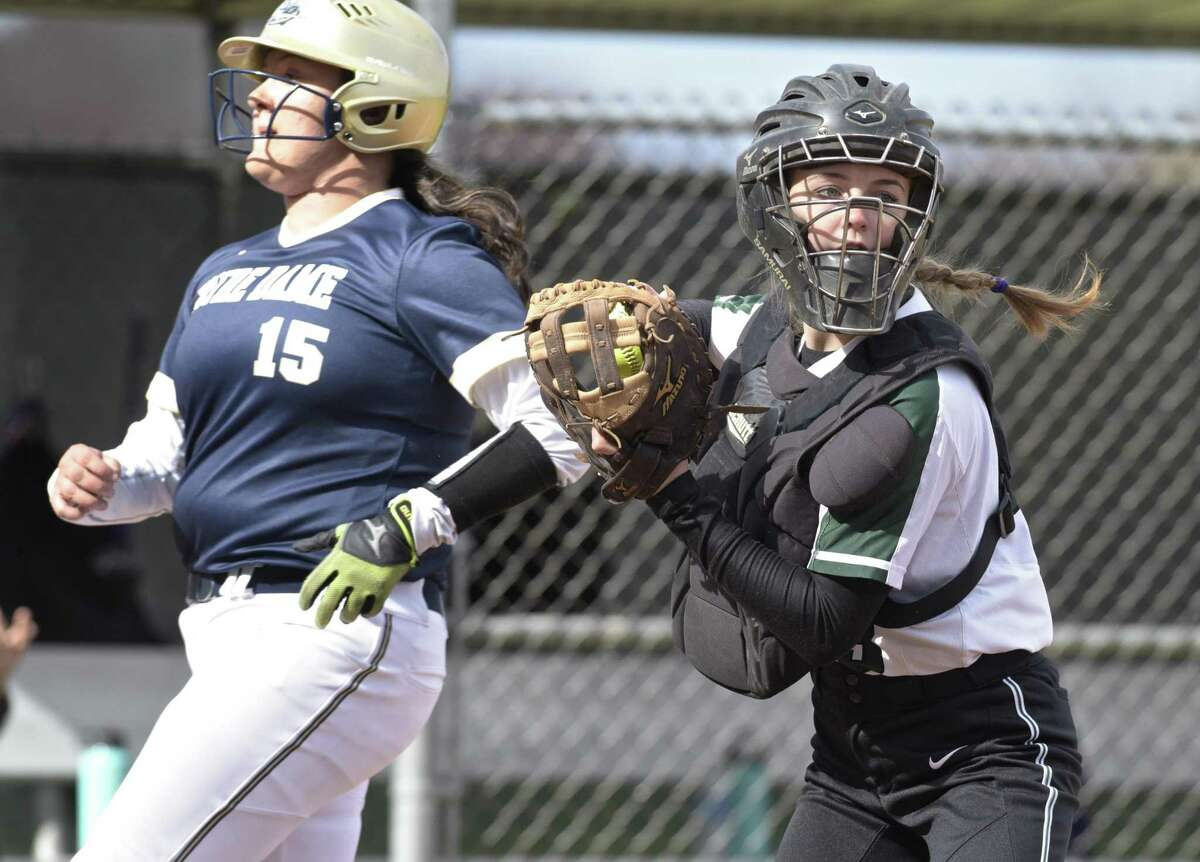 New Milford catcher Olivia Wetmore (13) looks at the base runners after the put out at home of Notre Dame's Meredith McDonald in the girls softball game between Notre Dame - Fairfield and New Milford high schools, Wednesday afternoon, April 18, 2018, at New Milford High School, New Milford, Conn.