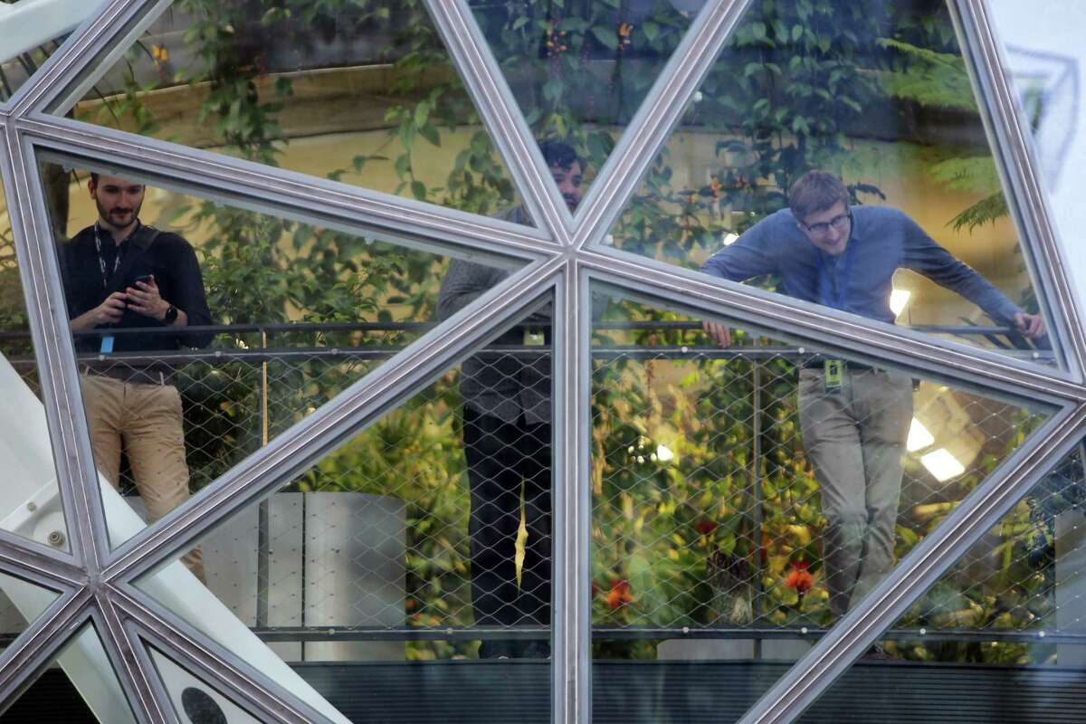 Amazon workers watch from the Spheres as the Seattle's 20th annual Immigrants' and Workers' Rights May Day demonstration passes by, Wednesday, May 1, 2019. Over 1,000 people marched from Judkins Park to the U.S. District Courhouse building downtown, making stops at the Chateau Apartments, Whole Foods and the Amazon Spheres along the way for short rallies.