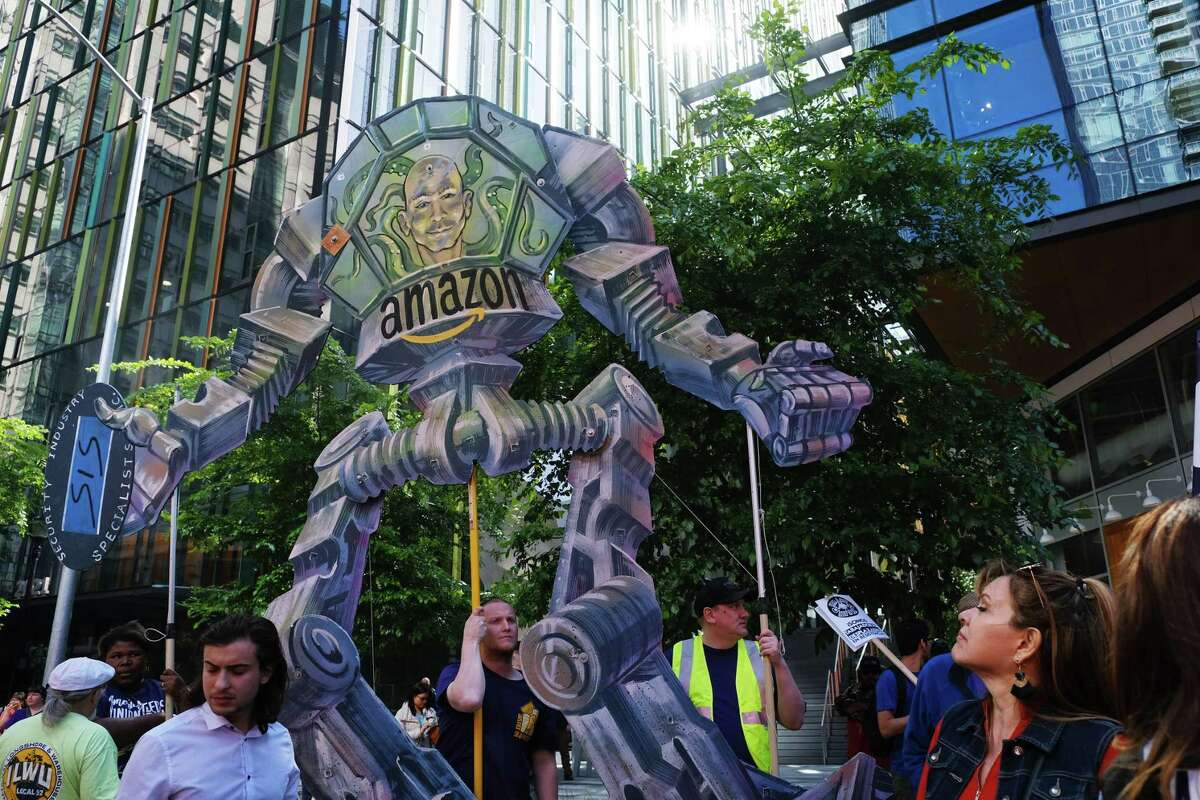 Seattle's 20th annual Immigrants' and Workers' Rights May Day demonstration passes by Amazon buildings, Wednesday, May 1, 2019. Over 1,000 people marched from Judkins Park to the U.S. District Courhouse building downtown, making stops at the Chateau Apartments, Whole Foods and the Amazon Spheres along the way for short rallies.