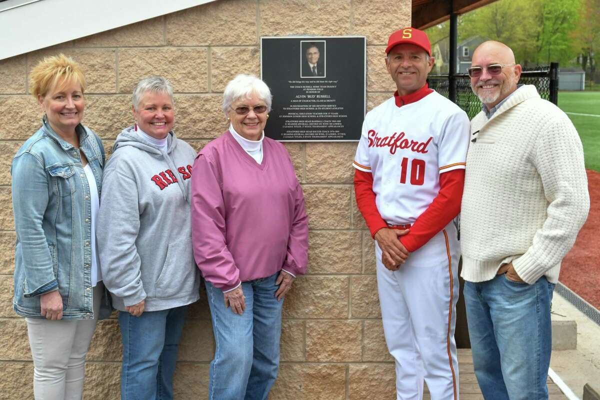 """Head Coach Mick Buckmir of the Stratford Red Devils stands with the Russell Family and plaque as the Home Team Dugout is dedicated to former coach Alvin """"Bud"""" Russell prior to a game against the Immaculate Mustangs on Wednesday May 1, 2019 at Penders Field in Stratford, Connecticut."""