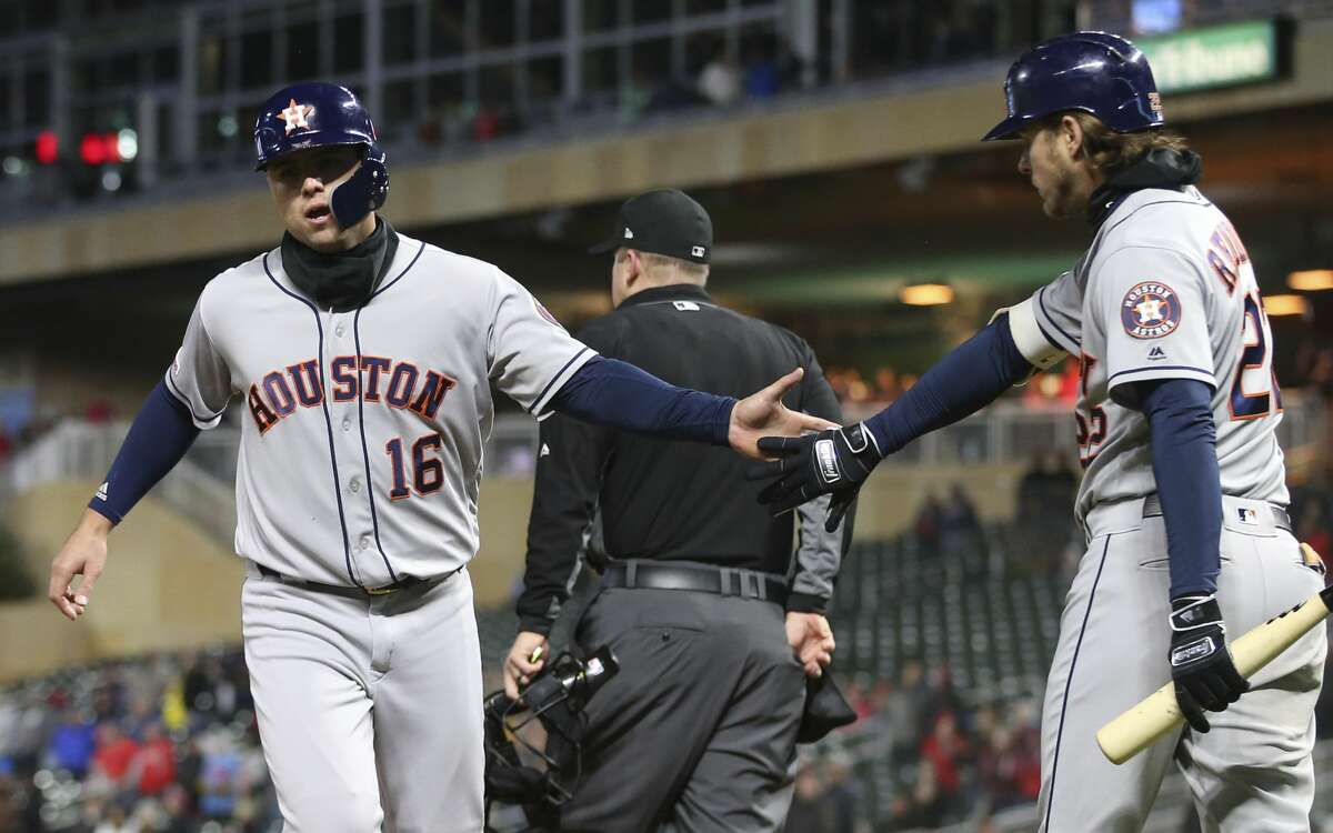 Houston Astros' Aledmys Diaz, left, is congratulated by Josh Reddick after Diaz scored on a hit by Tyler White off Minnesota Twins pitcher Trevor Hildenberger during the ninth inning of a baseball game Wednesday, May 1, 2019, in Minneapolis. The Twins won 6-2. (AP Photo/Jim Mone)