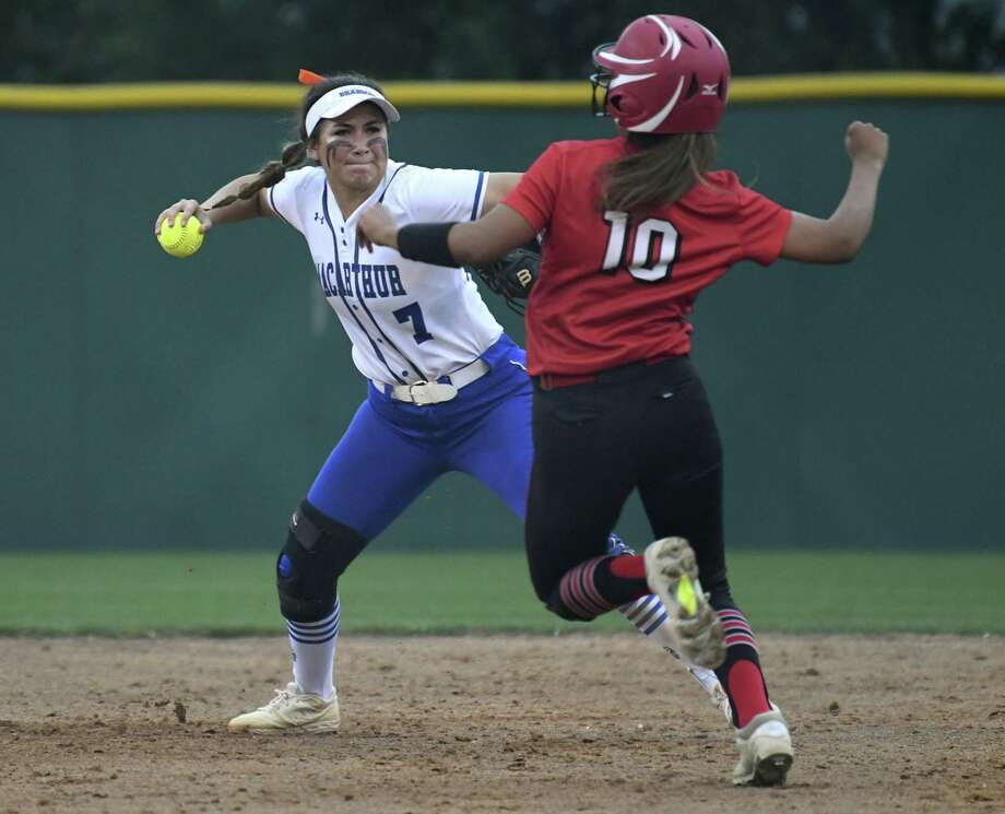 Taylor Medina (7) of MacArthur turns a double play as Isabel Armendariz of New Braunfels Canyon attempts to break it up during Game 1 of the UIL Class 6A second-round high school softball playoff series on Wednesday May 1, 2019. Photo: Billy Calzada, Staff / Staff Photographer / San Antonio Express-News