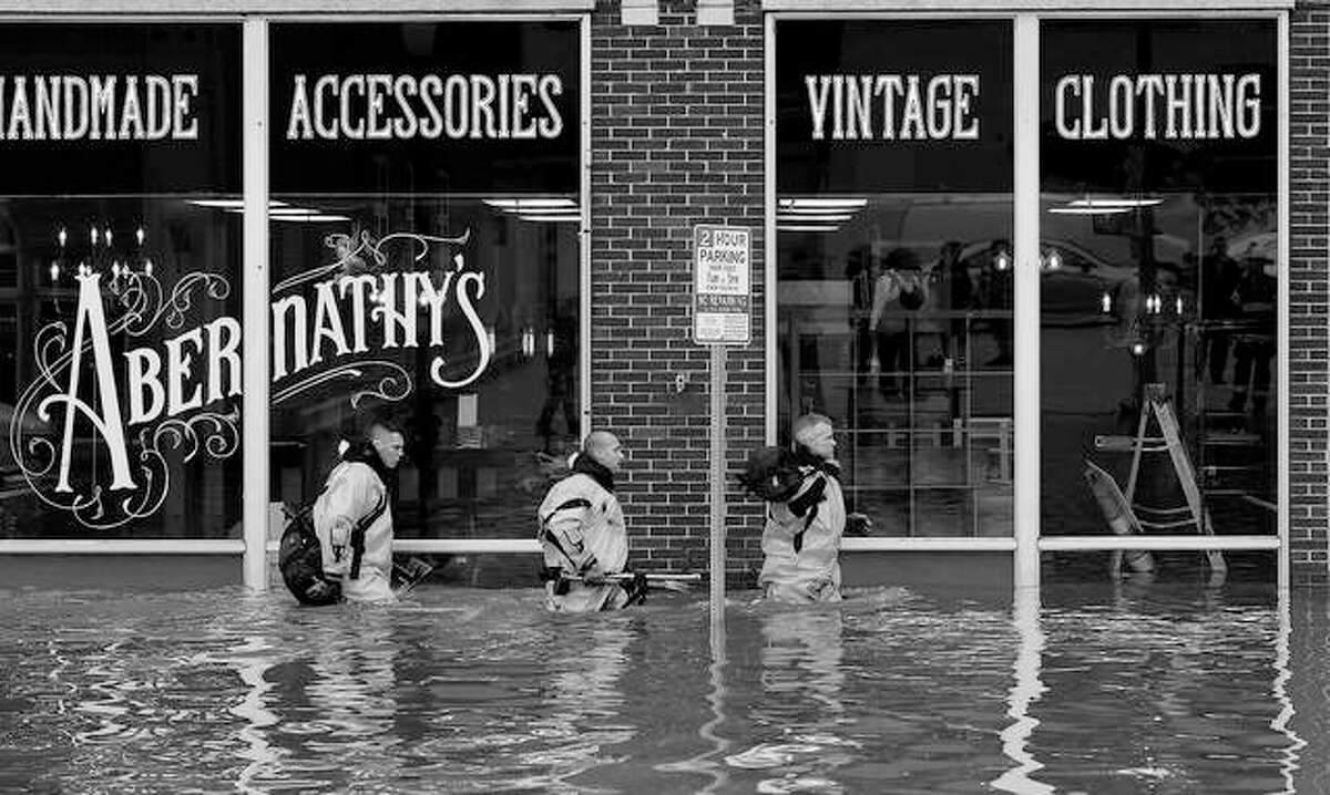 Firefighters move building to building checking for people trapped after the floodwall failed, sending Mississippi River floodwater into several blocks of downtown Davenport, Iowa.