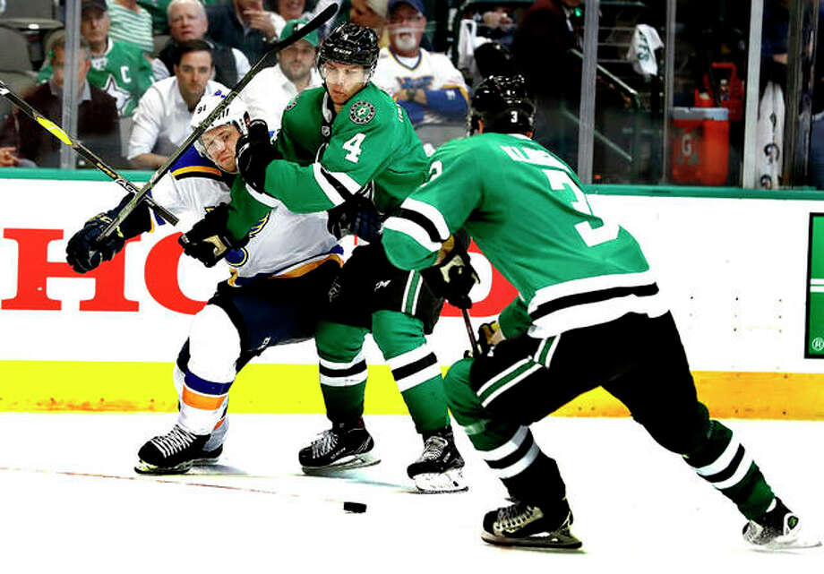 The Blues' Vladimir Tarasenko is pushed way by Dallas Stars' Miro Heiskanen (4) as the Stars' John Klingberg, right, reaches for the puck in the second period Wednesday night's Game 4 of their NHL second-round playoff series in Dallas. Photo: AP Photo