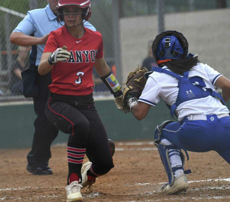 Mia Macchia of New Braunfels Canyon scores as MacArthur catcher Sarah Montes attempts to tag during Game 1 of the UIL Class 6A second-round high school softball playoff series on Wednesday May 1, 2019. Photo: Billy Calzada, Staff / Staff Photographer / San Antonio Express-News