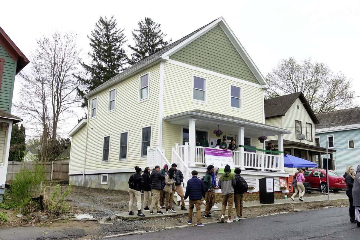 People gather for an event outside of a new net-zero home at 101 Prospect Street, that was built by YouthBuild Schenectady students in partnership with Saint-Gobain on Wednesday, May 1, 2019, in Schenectady, N.Y. (Paul Buckowski/Times Union)