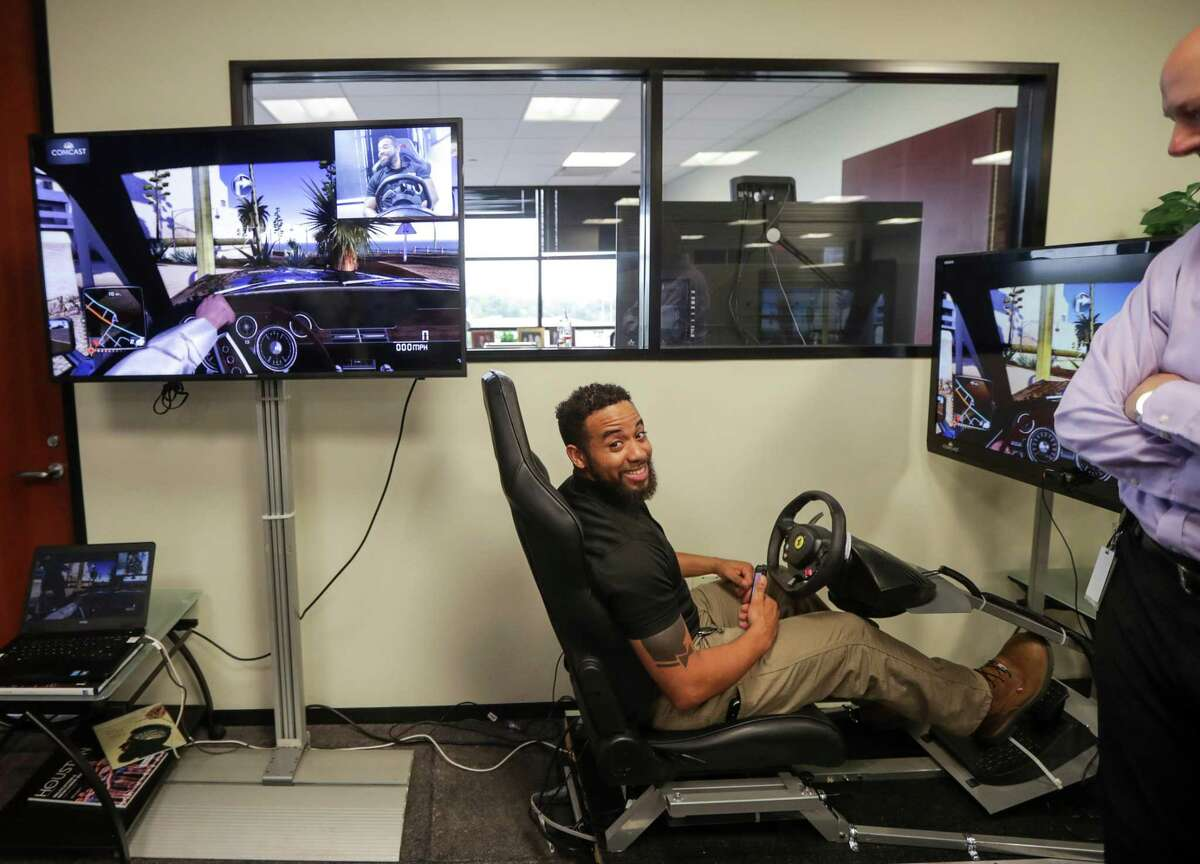 Sean Joseph, a technician with Comcast, smiles after crashing in a driving simulator while texting and driving at Comcast's Houston office on Tuesday, April 30, 2019, in Houston.
