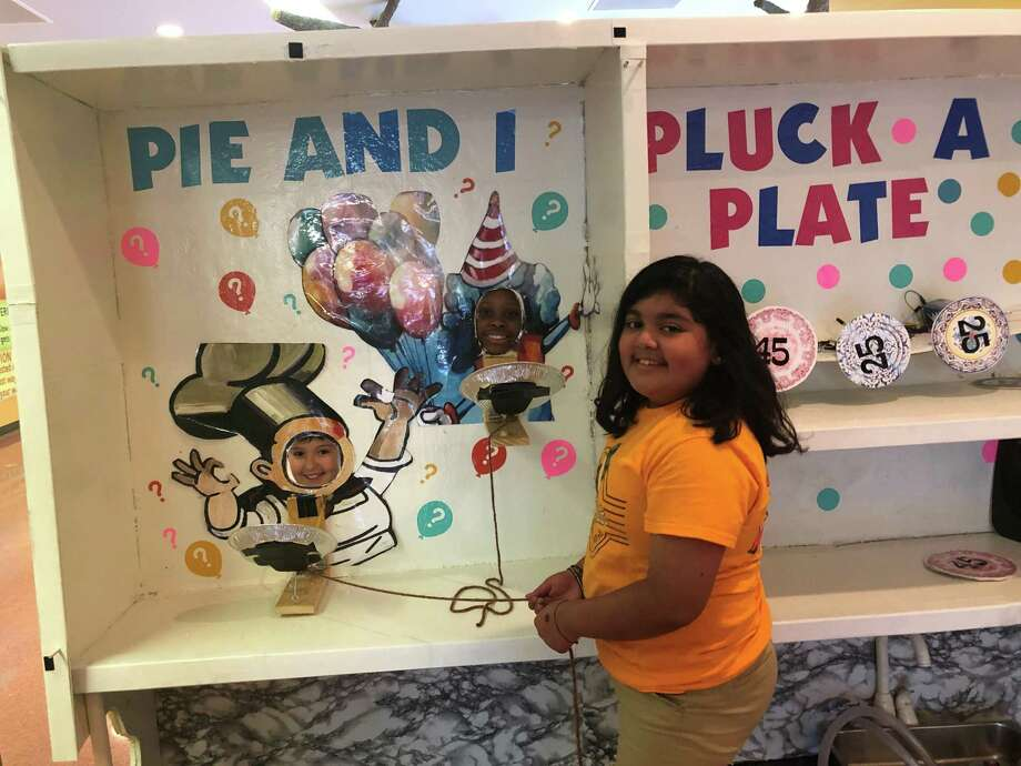 """Walnut Bend Elementary School students Daniella (left), Clarke and Melyna show off their specially rigged pie-in-the-face game that they will present as part of their """"Kitchen Carnival"""" performance at the 2019 Odyssey of the Mind World Finals later this month. Photo: Tracy Maness / Staff Photo"""
