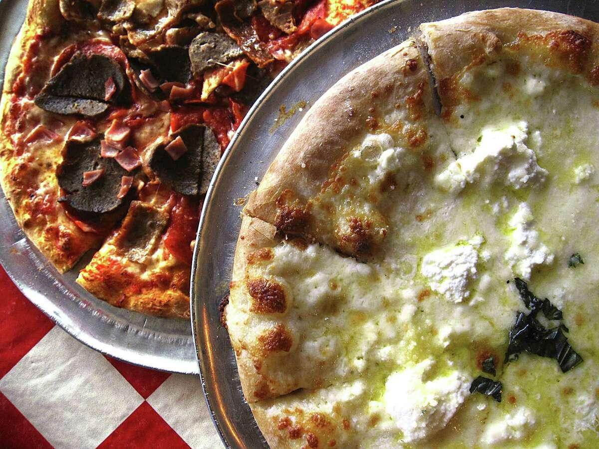 Pizza choices include a Tutta la Carne, left, with sausage, pepperoni, ham and meatballs and a Pizza Bianca with ricotta, provolone, feta, mozzarella and garlic at Julian's Italian Pizzeria & Kitchen.