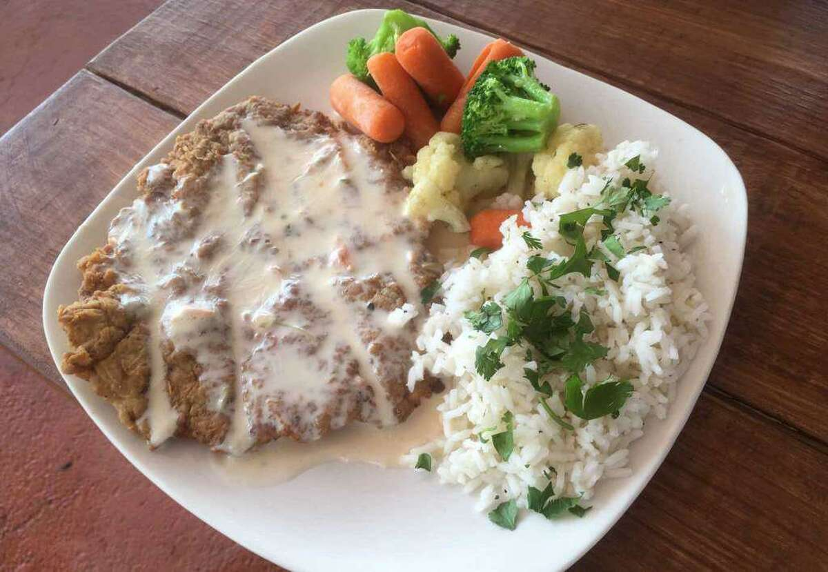 Chicken fried steak, topped with queso and sides of cilantro lime rice and mixed vegetables at The Patio Southtown