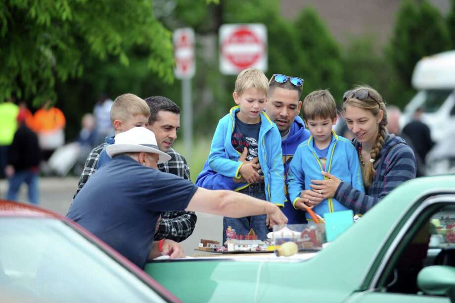 From right, Simone, Aaron, Nelson and Noah Franco, of Stamford, listen to Joe Anderson describe the small scene he has created, which features various vehicles and scenes from dozens of movies, during the third annual car and motorcycle show hosted by J.M. Wright Technical School at Scalzi Park on Bridge St. in Stamford, Conn. on Sunday, June 3, 2018. J.M. Wright Technical School will host its fourth annual car and motorcycle show at Scalzi Park, 120 Bridge St., May 19 from 10 a.m. to 3 p.m. Photo: Michael Cummo / Hearst Connecticut Media / Stamford Advocate